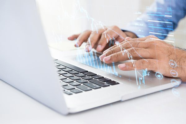 Businessman using online trading technology on laptop computer searching for digital data of stock for investment